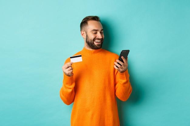 オンラインショッピング。インターネットで支払い、クレジットカードを持って携帯電話を見つめるひげを生やした男