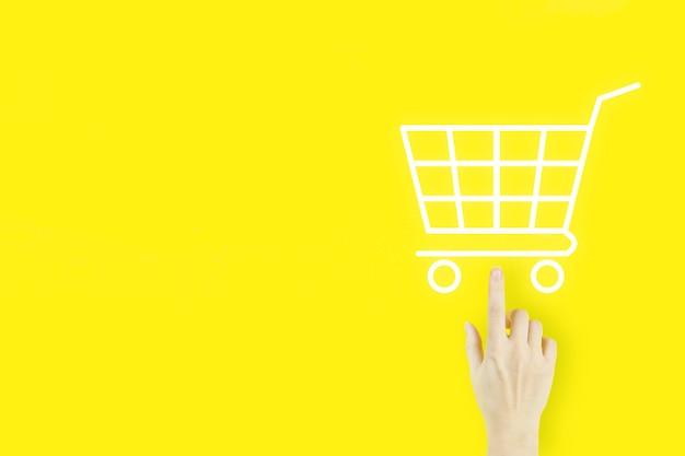 온라인 쇼핑 비즈니스 개념 쇼핑 카트를 선택합니다. 홀로그램으로 가리키는 젊은 여자의 손 손가락 노란색 배경에 쇼핑 카트입니다. 디지털 마케팅 온라인.