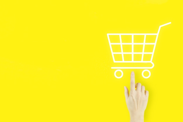 Online shopping business concept selecting shopping cart. young woman's hand finger pointing with hologram shopping cart on yellow background. digital marketing online.