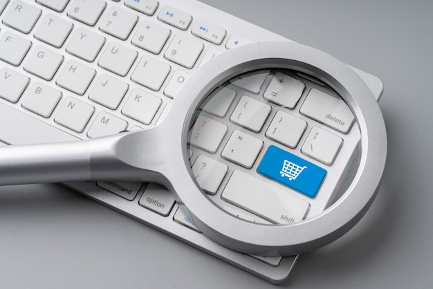 Online shopping & business icon on retro computer keyboard with magnifying glass