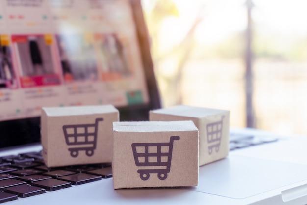 オンラインショッピング。ノートパソコンのキーボードにショッピングカートのロゴが入った段ボール箱。オンラインウェブ上のショッピングサービス。宅配を提供しています