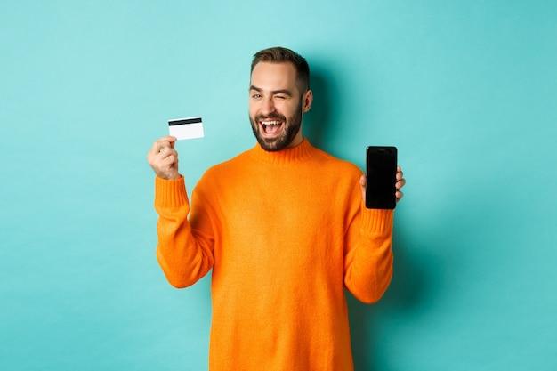 オンラインショッピング。クレジットカードとスマートフォンを見せて、カメラでウインクする白人男性