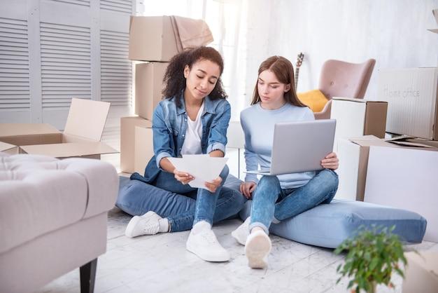 Онлайн шоппинг. очаровательные молодые девушки сидят на полу и просматривают таблицы цветов, выбирая краску для стен онлайн