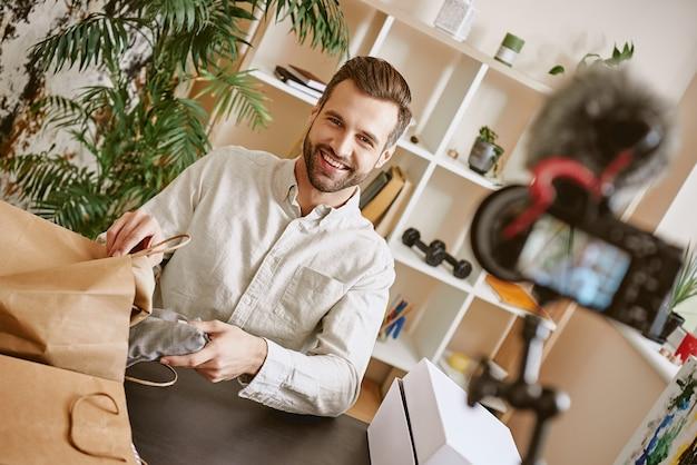 온라인 쇼핑 쾌활하고 젊은 남성 블로거가 삼각대에 온라인으로 새로 구매한 제품을 보여줍니다.