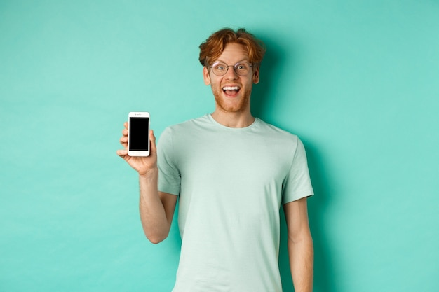 Online shopping. cheerful redhead man in glasses and t-shirt showing smartphone screen and smiling, standing over mint background.