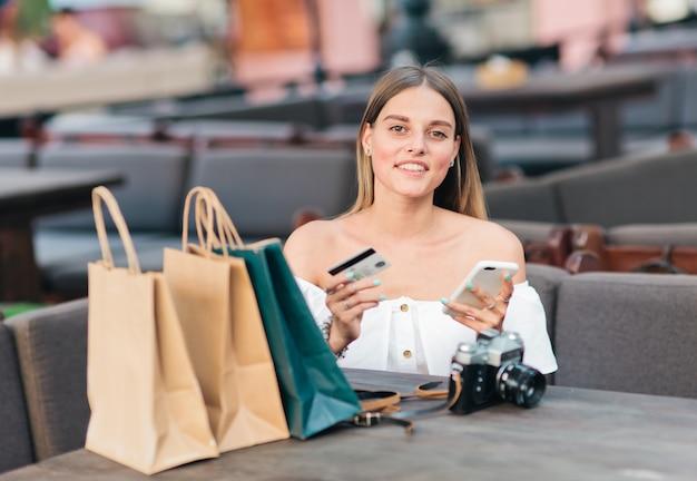 オンラインショッピング。陽気な女性が買い物袋を持つテーブルに座っているし、彼女の手のスマートフォンと屋外カフェで銀行カードを保持しています。