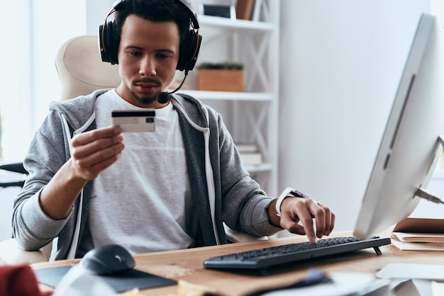 Online shopping. concentrated young man in casual clothing making a purchase online while spending time at home