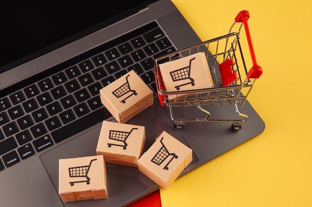 Концепция покупок в интернете. коробки на ноутбуке и корзине, изолированные на красочном фоне.