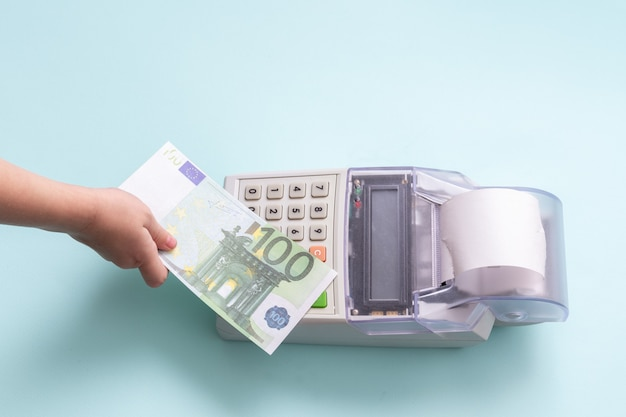 Концепция покупок в интернете. крупным планом рука ребенка, держащая банкноту 100 евро над кассовым аппаратом на синем фоне, вид сверху, место для копирования.