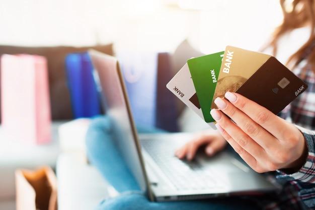 オンラインショッピングの概念。クレジットカードのクローズアップ。ラップトップでインターネットで買い物をする女性は、どちらのクレジットカードがより収益性が高いかを選択する必要があります。