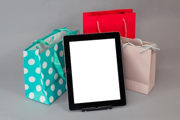 온라인 쇼핑 개념. 회색 배경에 밝은 선물 가방과 함께 흰색 화면으로 근접 태블릿 모형.