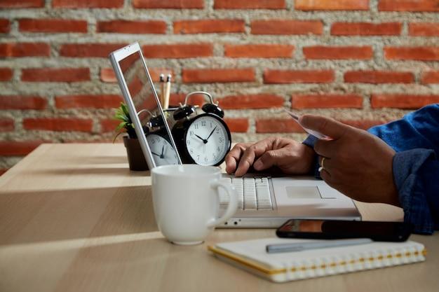 オンラインショッピングのコンセプト、テーブルの上のラップトップコンピューターでオンライン支払いを行うモバイルスマートフォンとクレジットカードを使用して若い男をクローズアップ