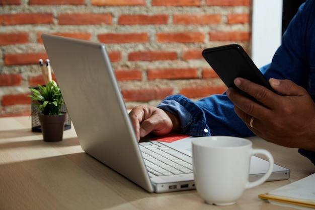 온라인 쇼핑 개념, 테이블 위에 노트북 컴퓨터로 온라인 결제를 하는 모바일 스마트폰과 신용 카드를 사용하여 젊은 남자를 닫습니다