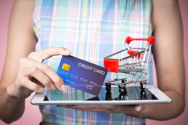 Online shopping concept. closeup of hand holding credit card with cart on tablet screen.