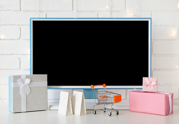 Online shopping concept. computer monitor and gifts and shopping for christmas.