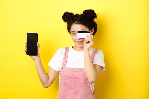 온라인 쇼핑 개념. 귀여운 아시아 여자 플라스틱 신용 카드로 지불, 빈 스마트 폰 화면을 표시하고 웃고, 노란색