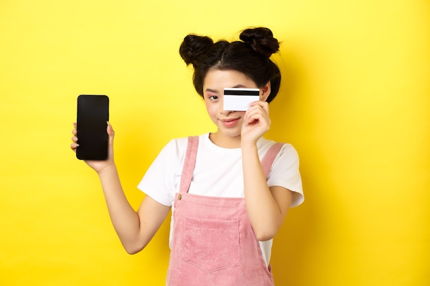 Online shopping concept. cute asian girl paying with plastic credit card, showing empty smartphone screen and smiling, yellow
