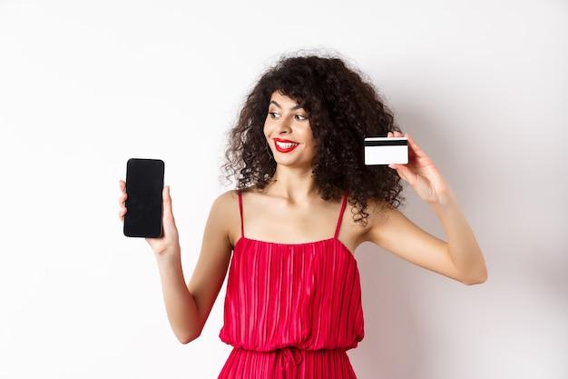 オンラインショッピングのコンセプト。白い背景の上に立って、プラスチックのクレジットカードと空の携帯電話の画面を示す赤いドレスのエレガントな縮れ毛の女性。