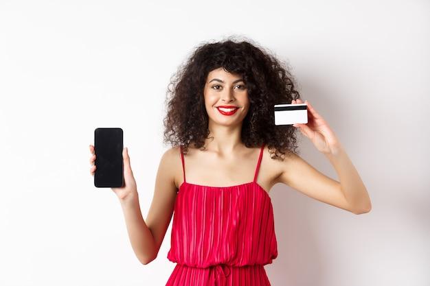 オンラインショッピングのコンセプト。巻き毛、赤いドレスを着て、白い背景の上に立って、空の携帯電話の画面でプラスチックのクレジットカードを示すエレガントな女性モデル。
