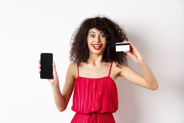 オンラインショッピングのコンセプト。空のスマートフォンの画面とプラスチックのクレジットカードを表示し、カメラで幸せそうに笑って、白い背景の上に立っている赤いドレスを着た興奮した縮れ毛の女性。