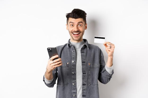 オンラインショッピングのコンセプト。インターネットで購入する興奮した男、プラスチックのクレジットカードとスマートフォンで簡単に購入、カメラに幸せな笑顔、白い背景。