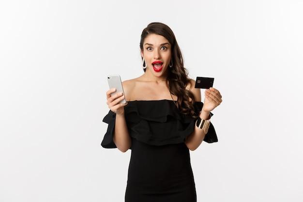 Концепция покупок в интернете. модная женщина в черном платье, держащая кредитную карту со смартфоном, выглядит взволнованно, стоя на белом фоне.