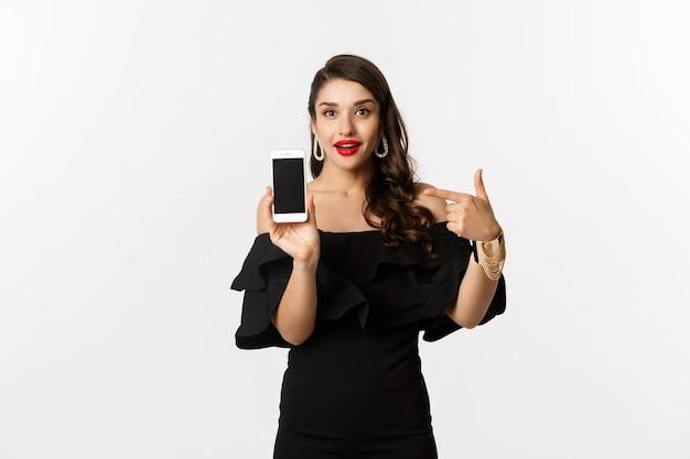 オンラインショッピングのコンセプト。スマートフォンの画面に指を指して、白い背景の上に立って、アプリケーションを示す黒いドレスのファッショナブルな女性。