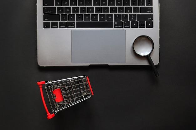 Концепция интернет-покупок продуктовая тележка для ноутбука и лупы на черном фоне