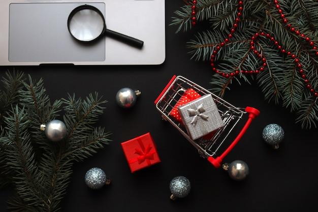 온라인 쇼핑 개념 선물 노트북 및 축제에 돋보기와 식료품 카트