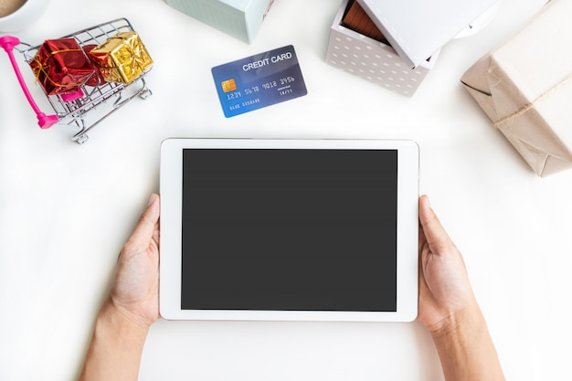 Online shopping concept. hand holding tablet, shopping cart, parcel boxes, credit card, on the desk at home. top view, copy space