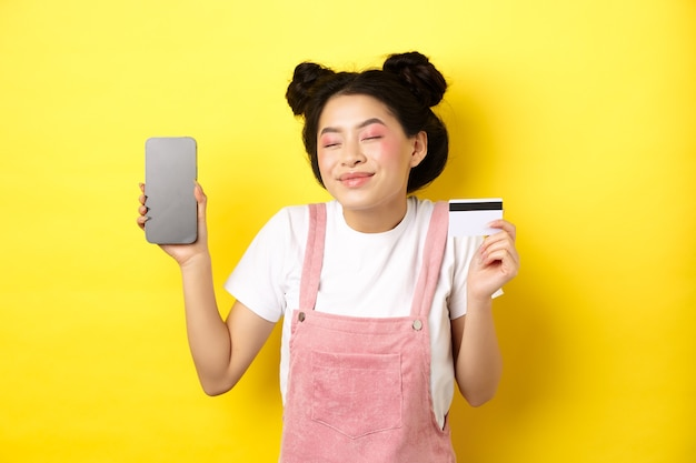 Online shopping concept. happy asian girl showing empty smartphone screen and credit card, paying contactless, standing on yellow
