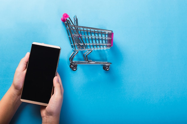 オンラインショッピングのコンセプト-水色の背景にスマートフォンとショッピングカートの画像。