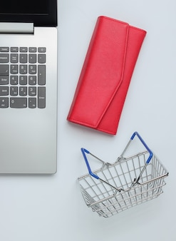 Online shopping concept laptop wallet and mini shopping basket on white background