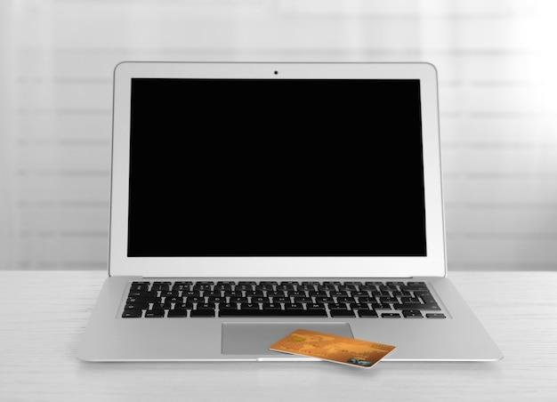 온라인 쇼핑 개념입니다. 나무 테이블에 신용 카드가 있는 노트북