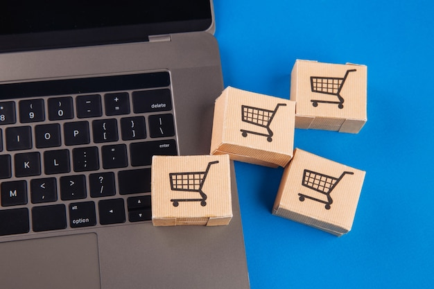 Концепция покупок в интернете. ноутбук с мини-коробками.