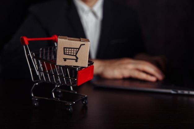 Концепция покупок в интернете. ноутбук с тележкой для мини-маркета и двумя бумажными коробками