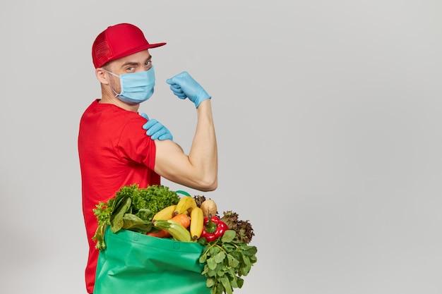 オンラインショッピングの概念。赤い制服を着た男性宅配便、防護マスク、新鮮な果物と野菜の食料品ボックス付き手袋。コロナウイルス検疫中の宅配食品