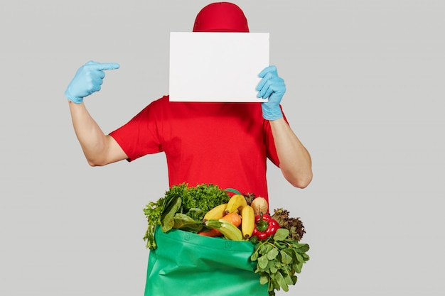 Online shopping concept. male courier in red uniform, protective mask and gloves with a grocery box with fruits and vegetables holds a white banner for text. home delivery food during quarantine