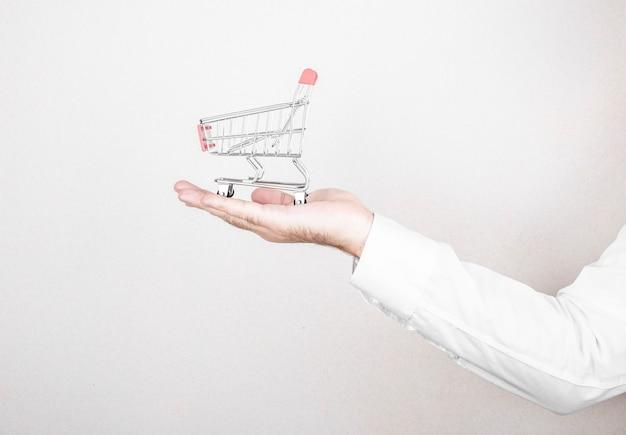 オンラインショッピングのコンセプト。男は壁の背景にショッピングカートを保持します。