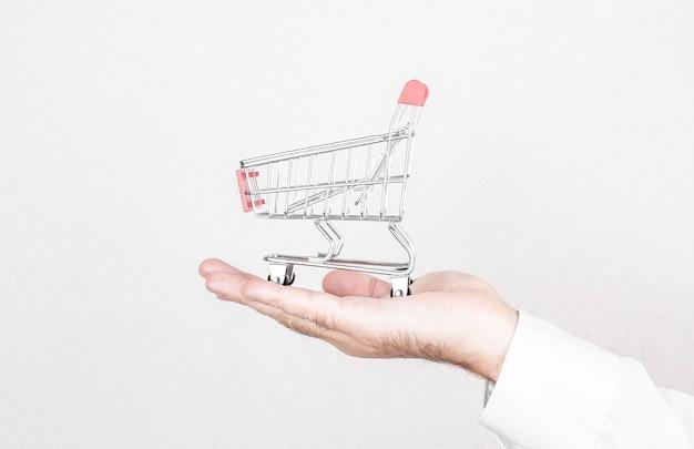 オンラインショッピングの概念男は壁にショッピングカートを保持します