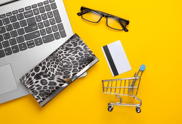 Online shopping concept. online supermarket. shopping trolley, bank card, wallet, laptop on a yellow. flat lay, top view