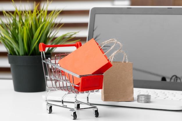 Online shopping concept. shopping cart, laptop on the desk
