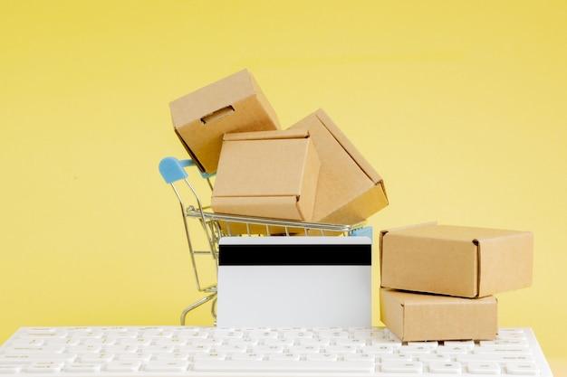 온라인 쇼핑 개념입니다. 노란색 배경에 작은 상자가 있는 쇼핑 카트. 물류 및 운송 관리 아이디어와 산업 비즈니스 상업 개념.