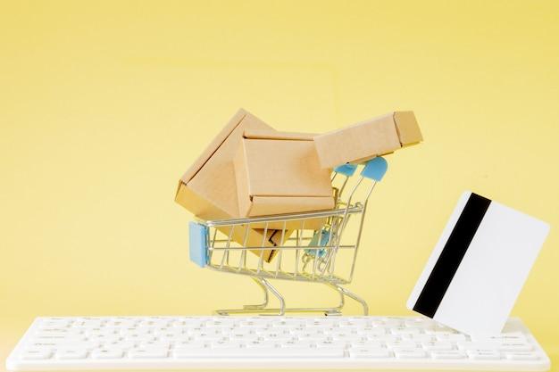 オンライン ショッピングのコンセプト。黄色の背景に小さな箱が入ったショッピング カート。物流と輸送管理のアイデアと産業ビジネスの商業コンセプト。