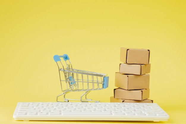 Online shopping concept. shopping cart with small boxes inside on yellow background