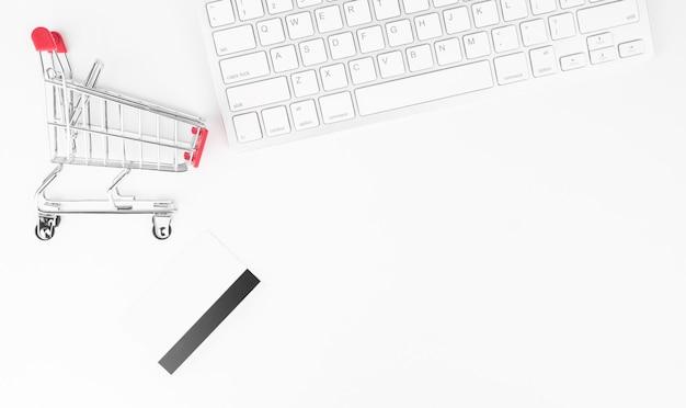 온라인 쇼핑 개념. 작은 빨간 트롤리, 키보드 및 테이블에 신용 카드.