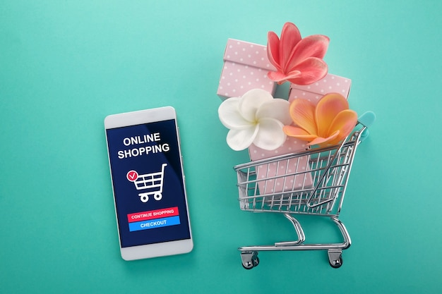Online shopping concept. smart phone with shopping cart on mint background. top view
