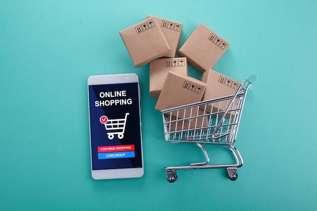 オンラインショッピングのコンセプト。ミントの背景にショッピングカート付きのスマートフォン。上面図。