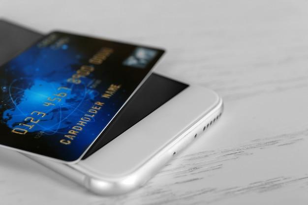 온라인 쇼핑 개념입니다. 나무 배경에 신용 카드가 있는 스마트폰, 근접 촬영