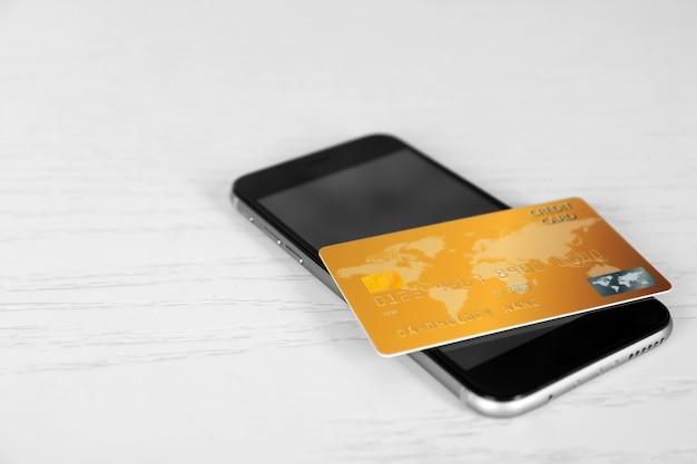 온라인 쇼핑 개념입니다. 나무 배경에 신용 카드가 있는 스마트폰